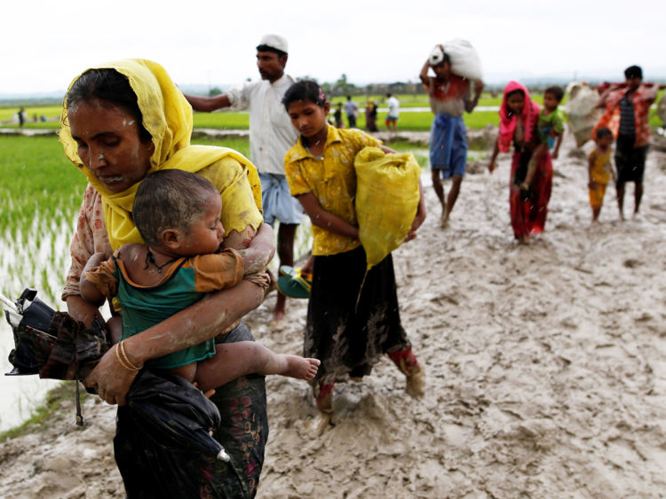 A Rohingya refugee woman carry a child while walking on the muddy road after travelling over the Bangladesh-Myanmar border in Teknaf, Bangladesh, September 1, 2017. REUTERS/Mohammad Ponir Hossain - RC1305D86090