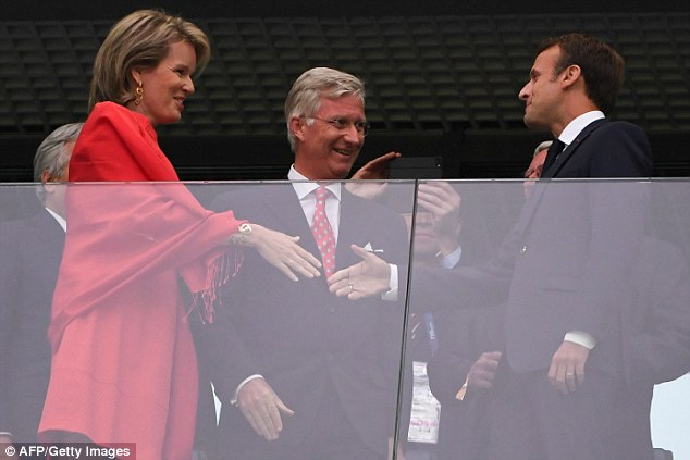 French President Emmanuel Macron greets Belgium's Queen Mathilde and King Philippe as they prepare to watch their countries do battle