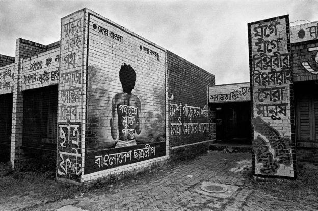 ১৯৯০ সালে এ ছবিটি তোলেন শহিদুল আলম। ঢাকা বিশ্ববিদ্যালয় ক্যাম্পাসে নূর হোসেন স্মরণে এ ম্যুরাল তৈরি করা হয়েছিল।